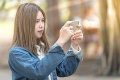 Kobieta używa telefon komórkowego bierze fotografię Zdjęcie Royalty Free