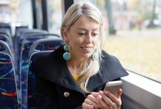 Kobieta używa telefon komórkowego podczas gdy jadący publicznie transport Zdjęcie Stock