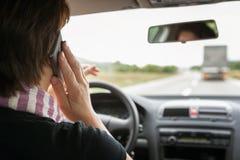 Kobieta używa telefon komórkowego podczas gdy jadący samochód fotografia stock