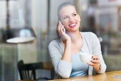 Kobieta używa telefon komórkowego przy kawiarnią Fotografia Royalty Free