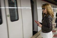 Kobieta używa telefon komórkowego przy stacją metru fotografia stock