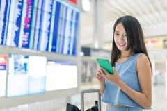 Kobieta używa telefon komórkowego sprawdzać jej lota rozkład Obrazy Royalty Free