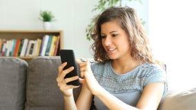 Kobieta używa telefon komórkowego w domu zdjęcie wideo