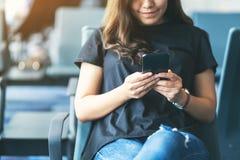 Kobieta u?ywa telefon kom?rkowego w lotnisku podczas gdy siedz?cy obraz royalty free