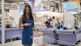 Kobieta używa telefon komórkowego w supermarkecie podczas gdy robiący zakupy, tramwaju centrum handlowego sklepu spożywczego skle zdjęcie wideo