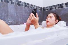 Kobieta używa telefon komórkowego w wannie w łazience Obrazy Stock