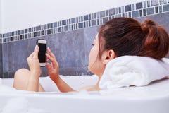 Kobieta używa telefon komórkowego w wannie w łazience Zdjęcie Royalty Free