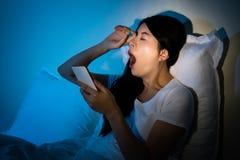 Kobieta używa telefon naciera ona oczy i poziewanie obraz royalty free