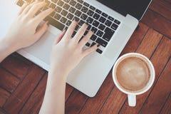 Kobieta używa laptop pracuje na drewnianym stole zdjęcie stock