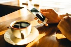 Kobieta u?ywa smartphone na drewnianym stole w kawiarni obraz royalty free