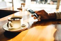 Kobieta u?ywa smartphone na drewnianym stole w kawiarni obraz stock