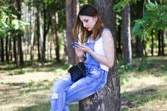 Kobieta używa smartphone w lesie Obraz Stock