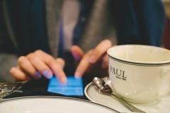 Kobieta używa smartphone w Paul cukiernianym pije cofee Obraz Royalty Free