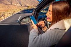 Kobieta używa smartphone w samochodzie Zdjęcia Stock
