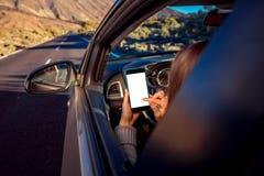 Kobieta używa smartphone w samochodzie Obraz Royalty Free