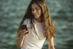 Kobieta używa telefon komórkowego morzem Zdjęcie Royalty Free