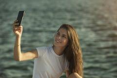 Kobieta używa telefon komórkowego morzem Fotografia Royalty Free