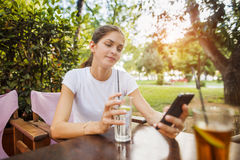 Kobieta używa telefon komórkowego przy parkiem Obraz Stock