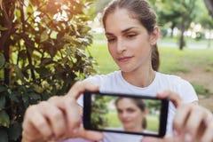 Kobieta używa telefon komórkowego przy parkiem Fotografia Royalty Free