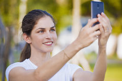 Kobieta używa telefon komórkowego przy parkiem Zdjęcia Royalty Free