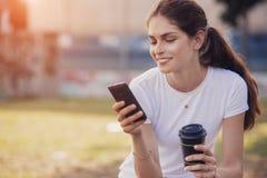 Kobieta używa telefon komórkowego przy parkiem Zdjęcia Stock