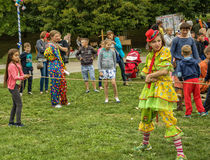 Kobieta ubierał w błazenu kostiumowych sztukach z dziećmi w fr Obrazy Royalty Free