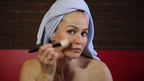 Kobieta ubierał w kąpielowym ręczniku stosuje tonalnego proszek twarz stosowanie opieki skóry przejrzystego lakier dzienna facial zdjęcie wideo
