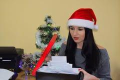 Kobieta ubiera w Santa ` s nakrętce Biurowa poczta jest w pudełku Nowego Roku ` s dowcip Fotografia Royalty Free