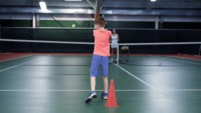 Kobieta ubierająca w białym sporta stroju bawić się tenisa z jej synem przy salowym sądem Kobieta trener słuzyć i chłopiec jest zdjęcie wideo