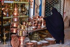 Kobieta, ubierająca w Islamskiej przesłonie, kupuje miedzianych naczynia w bazarze Obraz Royalty Free