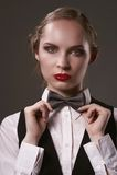 Kobieta ubierająca w kostiumu i łęku krawacie Zdjęcia Royalty Free
