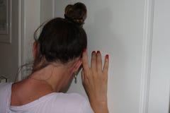 Kobieta ucho naciskający drzwi z słuchaniem co zdarza się w następnym pokoju zdjęcie royalty free
