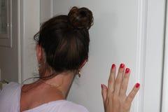 Kobieta ucho naciskający drzwi z słuchaniem co zdarza się w następnym pokoju Zdjęcie Stock