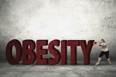 Kobieta uderza pięścią otyłości słowo z bokserskimi rękawiczkami Fotografia Stock