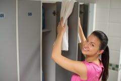 Kobieta umieszcza ręcznika na szafki drzwi Zdjęcia Royalty Free