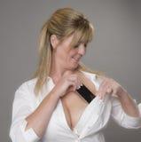 Kobieta umieszcza telefon w jej stanika Zdjęcia Royalty Free