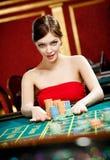 Kobieta umieszcza zakład przy uprawia hazard domem fotografia royalty free