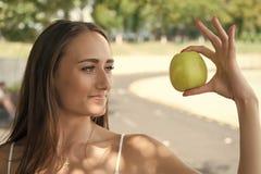 Kobieta uroczych i zdrowych chwyt?w zielony jab?ko Sekret jej pi?kno jest zdrowym od?ywianiem Dziewczyny poparcie lub dieting zdjęcie stock
