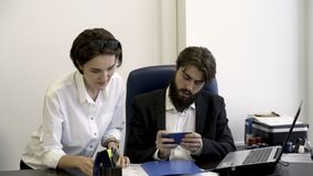 Kobieta, urzędnik pokazuje znacząco dokumenty jej brodaty szef który jest ruchliwie z bawić się mądrze telefon gry w fotografia royalty free