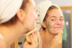 Kobieta usuwa twarzową glinianą błoto maskę w łazience fotografia stock