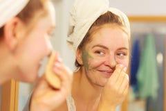 Kobieta usuwa twarzową glinianą błoto maskę w łazience obraz royalty free