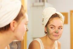 Kobieta usuwa twarzową glinianą błoto maskę w łazience fotografia royalty free