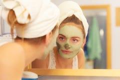 Kobieta usuwa twarzową glinianą błoto maskę w łazience zdjęcie royalty free