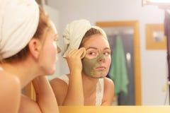 Kobieta usuwa twarzową glinianą błoto maskę w łazience zdjęcia royalty free