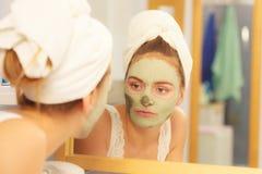 Kobieta usuwa twarzową glinianą błoto maskę w łazience zdjęcia stock