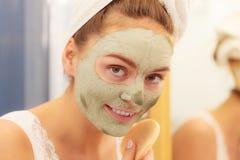 Kobieta usuwa twarzową glinianą błoto maskę w łazience obrazy stock