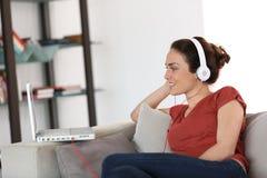 Kobieta używa hełmofony i laptop Zdjęcie Royalty Free