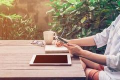 Kobieta używa telefon na stołowym drewnie w ogródzie przy sklep z kawą Zdjęcia Royalty Free