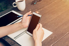 Kobieta używa telefon na stołowym drewnie w ogródzie przy sklep z kawą z vi Zdjęcia Stock