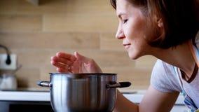 Kobieta wącha ładnych aromaty od jej posiłku w garnku, zamyka up zdjęcie wideo